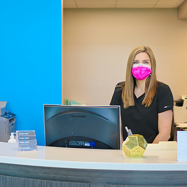 A friendly receptionist wearing a mask at Singing River Dentistry