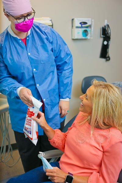 An assistant giving a patient care package at Singing River Dentistry